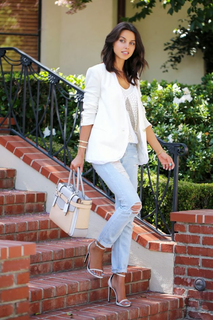 Annabelle Fleur is wearing a beaded top from Assali Ghysele, white twisted blazer from Helmut Lang, tote from Reed Krakoff and ankle straps from Saint Laurent