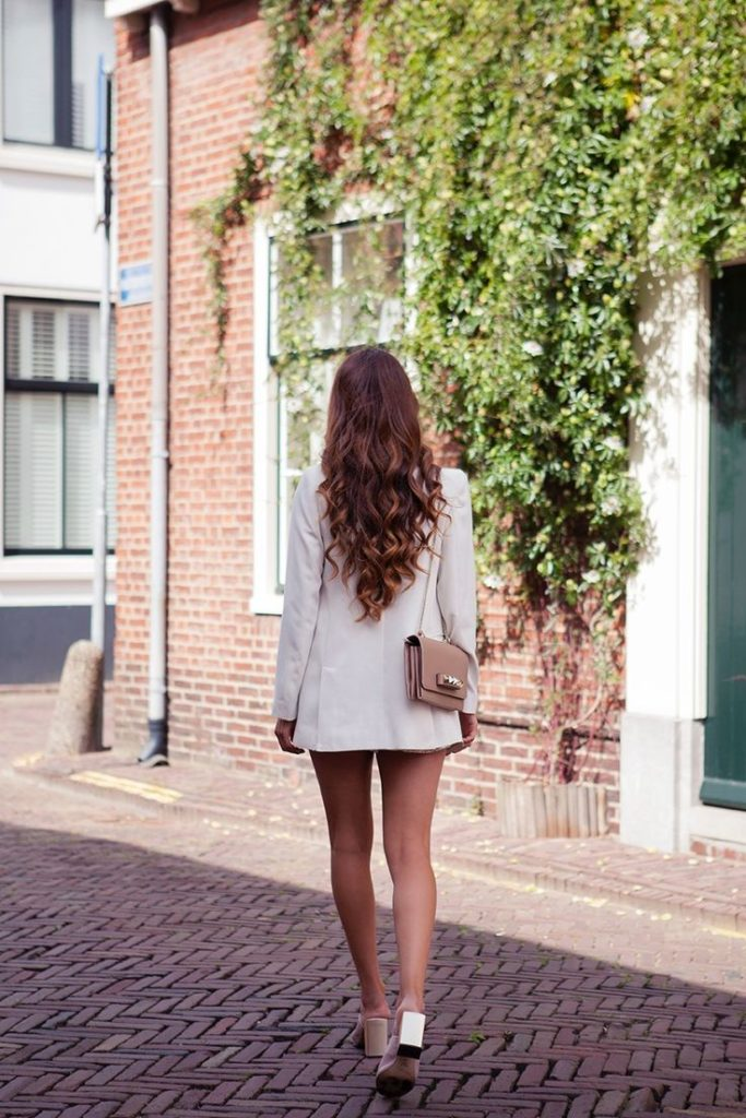 Negin Mirsalehi is wearing a white blazer from Mango and shoes from nude mules from Zara