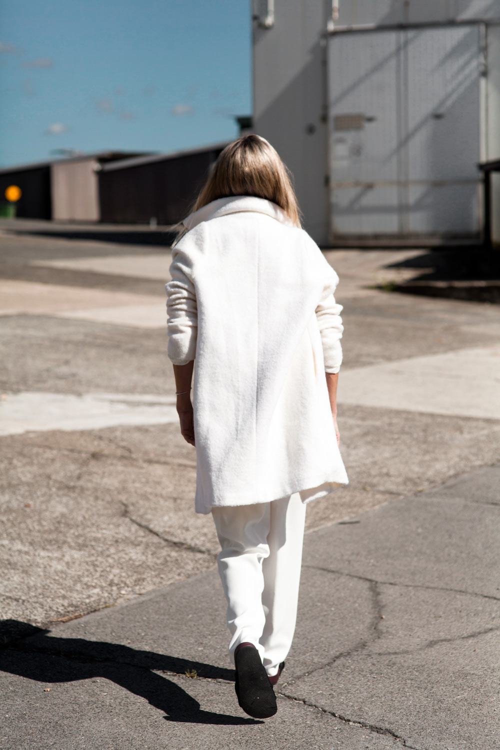 Mandy Shadforth is wearing all white. Oversized white coat from Carven, grey T-shirt and and white trousers from Ellery