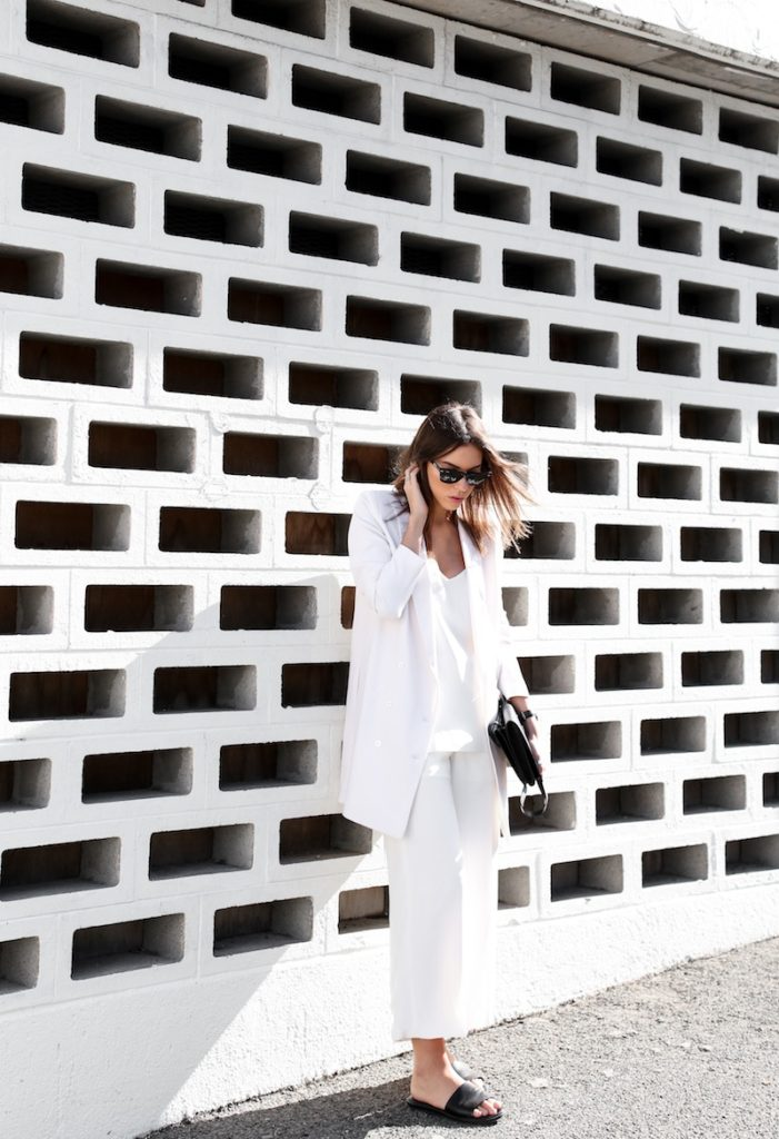 Kaitlyn Ham is wearing a white blazer from Rodebjer, wide leg silk culotte shorts, cami from Camilla and Marc, slides from Common Projects and the clutch is from Alexander Wang