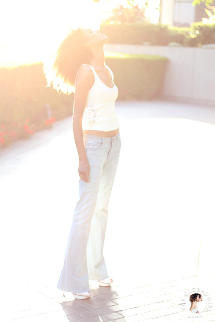 Ndoema is wearing low rise flare striped jeans from J Brand and white leather crop top