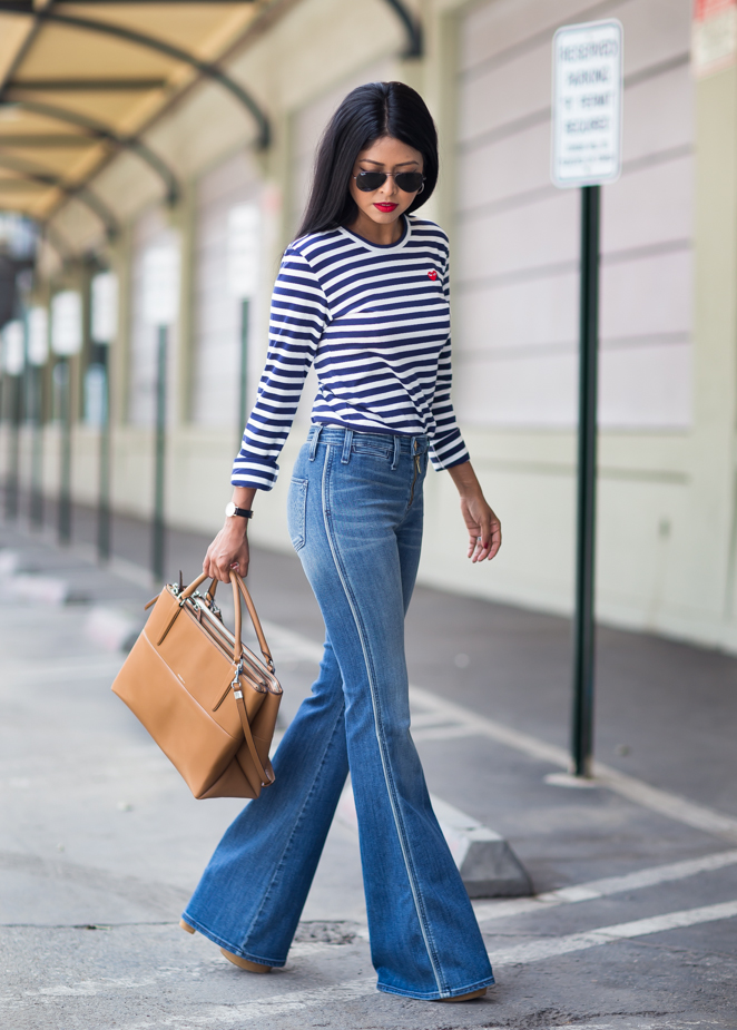Sherul Luke is wearing a striped top and flare jeans from Ron Herman and bag from Coach