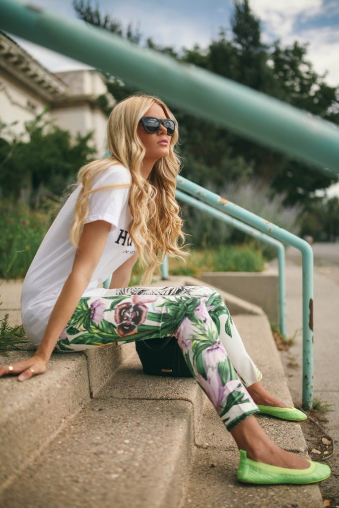 Barefoot Blonde Is Wearing Floral Trousers From Revolve Clothing, T-Shirt From ASOS, Shoes From Yosi Samra,Sunglasses From Westward Leaning