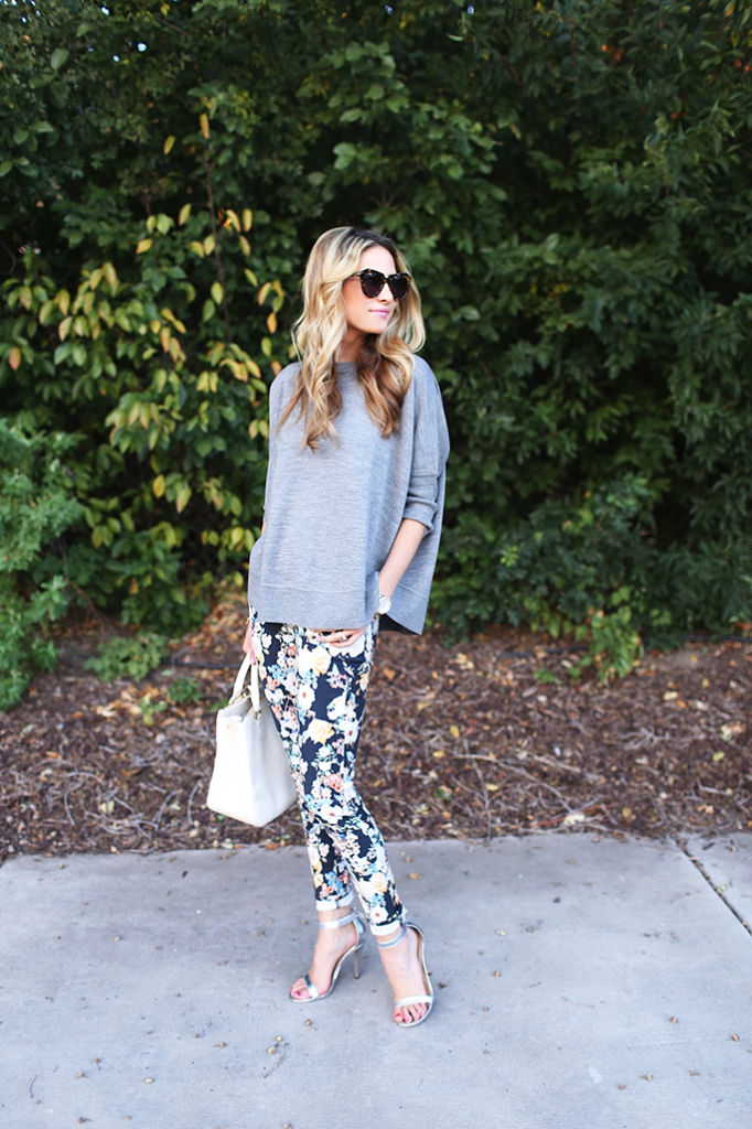 Emily Jackson is wearing a grey top from J. Crew, floral pants from 7FAM, silver sandals from Lulu's, white bag from Tony Burch and sunglasses from Karen Walker