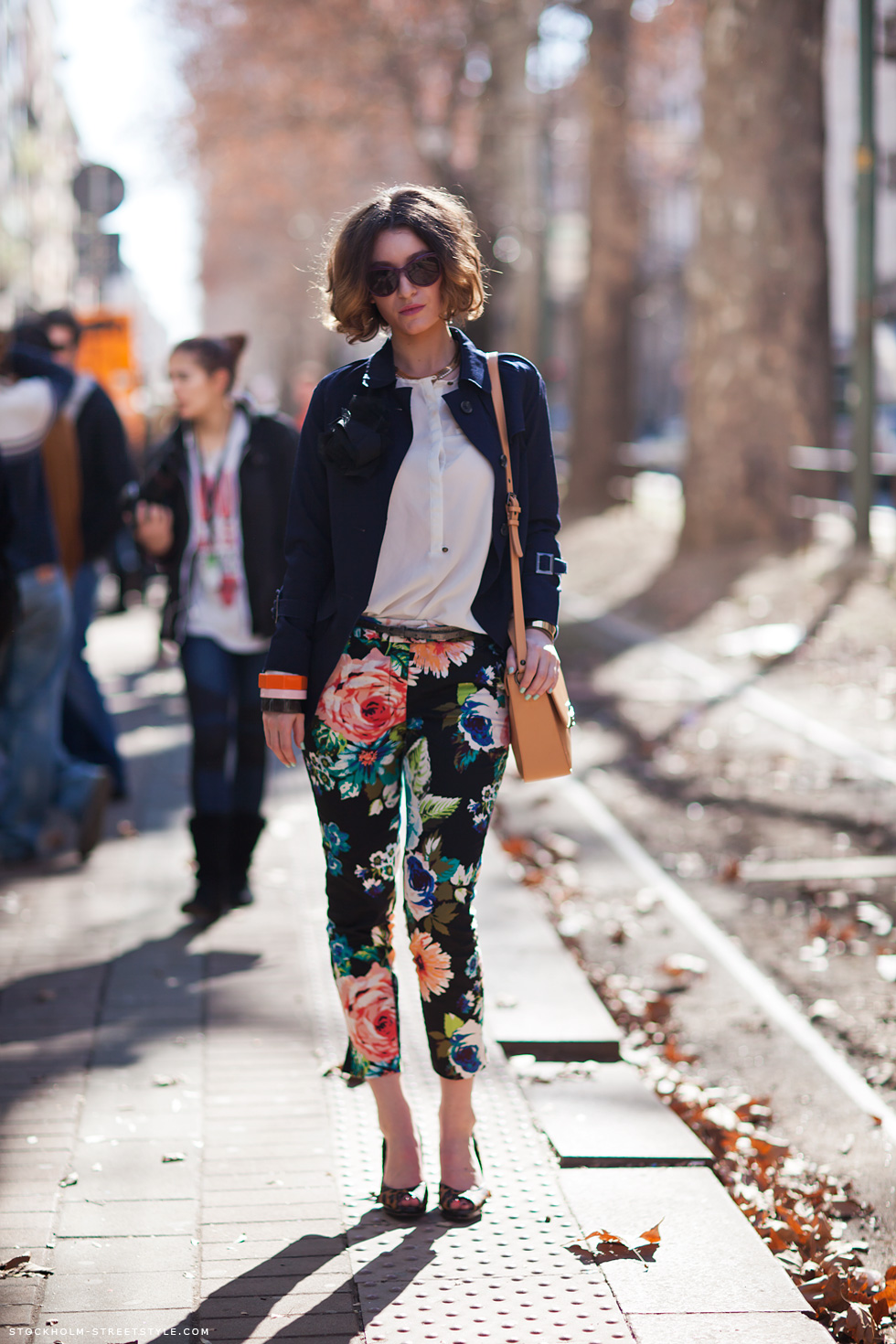 Colette is wearing a blue shirt, white tee and floral pants and shoes Via Stockholm Street Style