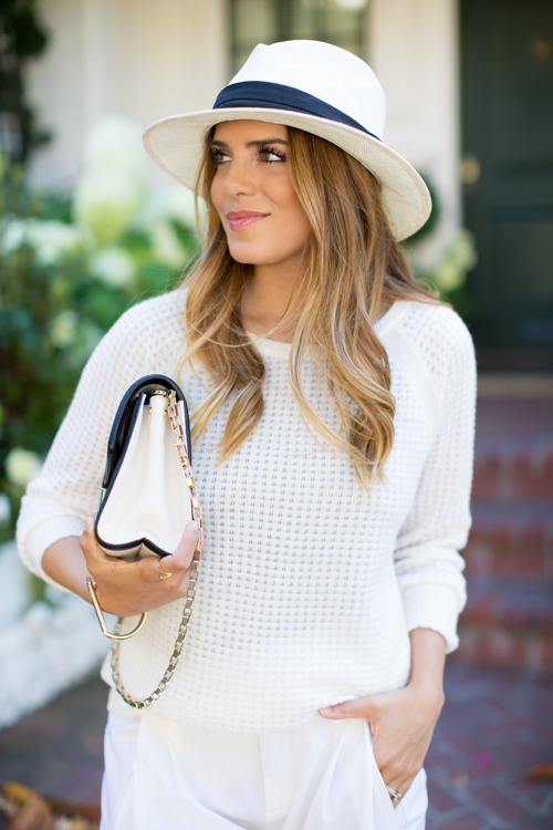 Julia Engel is wearing a mesh sweater from Vince, hat from Free People and clutch from Kate Spade