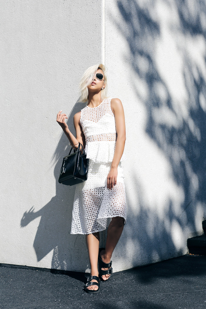 Vanessa Hong is wearing a white mesh dress from Self Portrait, sandals from Senso and the bag is from Fendi