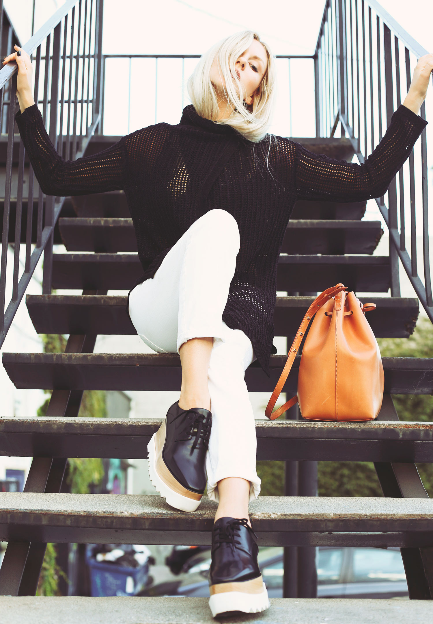 Shea Marie is wearing a black mesh sweater from Elie Tahari, shoes from Stella McCartney and a bag from Mansur Gavriel