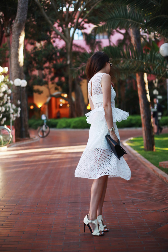 Andy Torres is wearing a white mesh dress from Self-Portrait and shoes from Acne