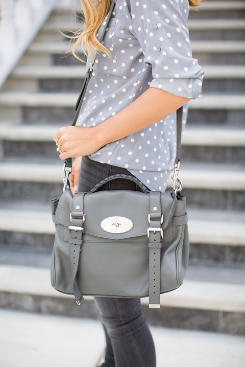 Julia Engel is wearing a grey and white polka dot shirt and grey jeans both from Express and the bag is from Mulberry