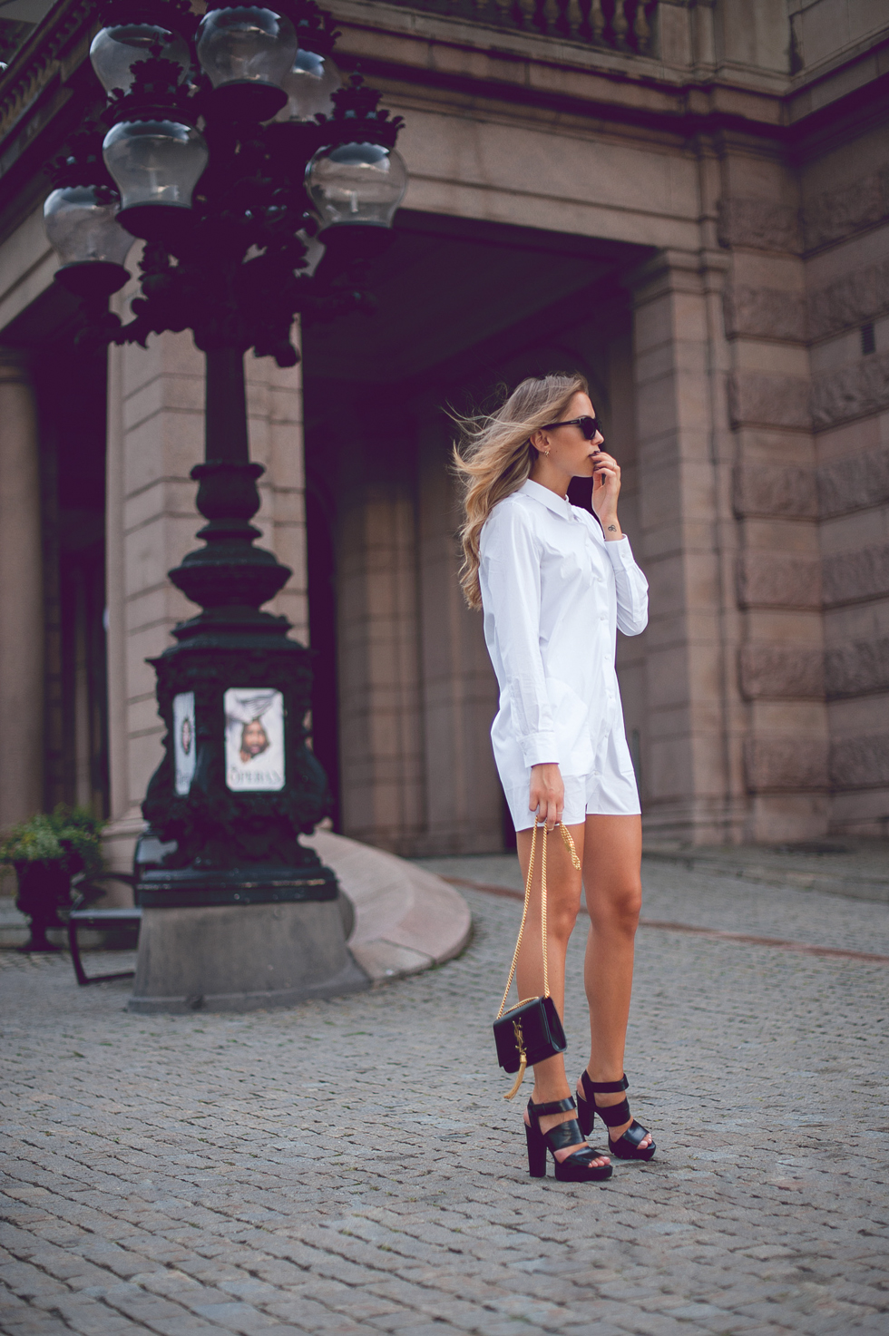 Kenza Zouiten is wearing a crisp whiye shirt dress from Acne, bag from Saint Laurent, sunglasses from Prada and shoes from Zara