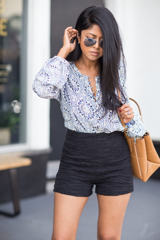Sheryl Luke is wearing a paisley top from Fifteen Twenty, black short shorts from Zara and the bag is from Coach