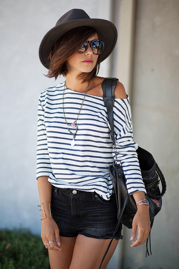 Zoe Jonak is wearing a striped off the shoulder top from H&M, short shorts from Levi's, bag from Balenciaga and sunglasses and hat from Urban Outfitters