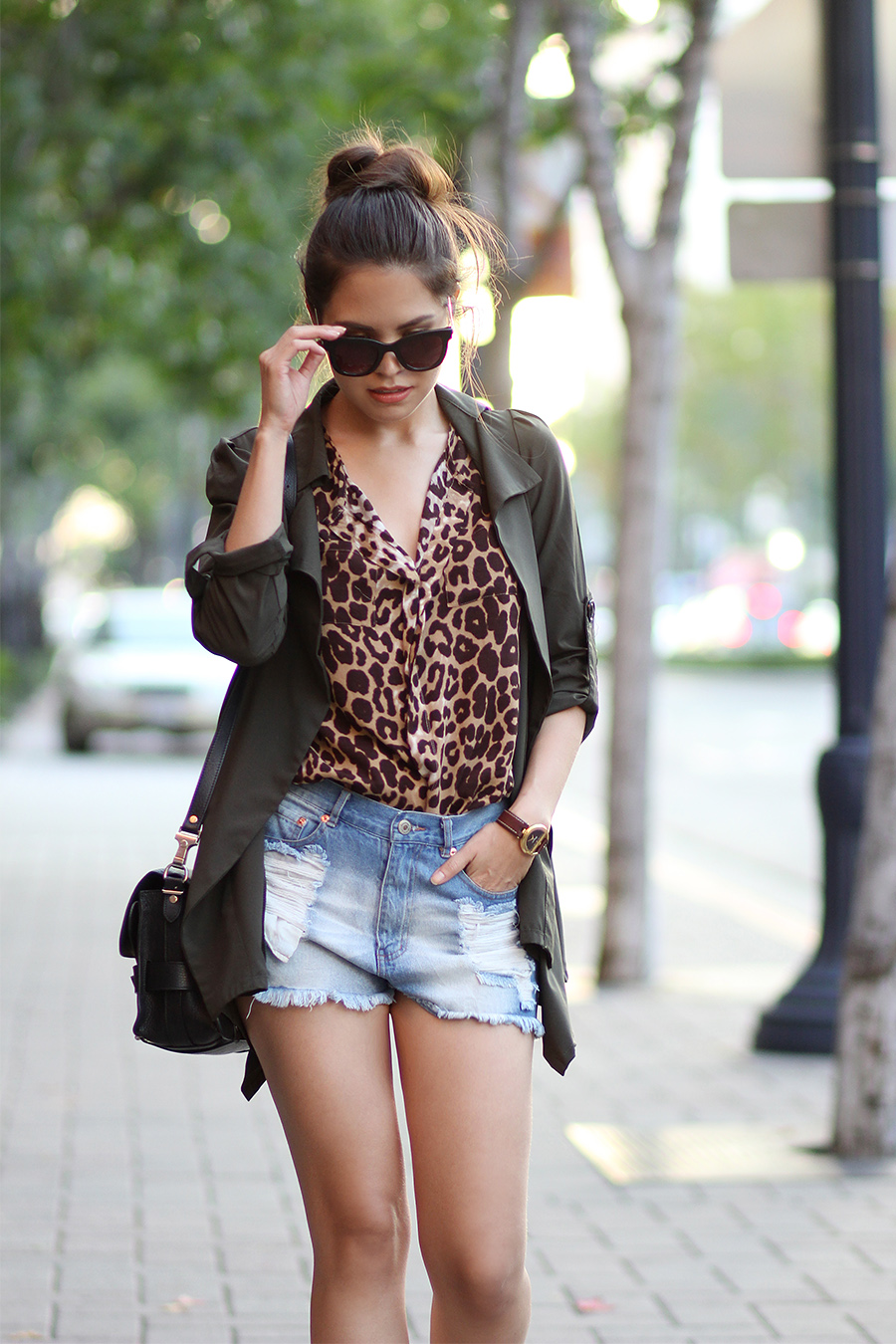 Adriana Gastelum is wearing a green trench coat from Papaya, leopard print top from Windsor, ripped denim shorts from Forever21 and a bag from Proenza Schouler