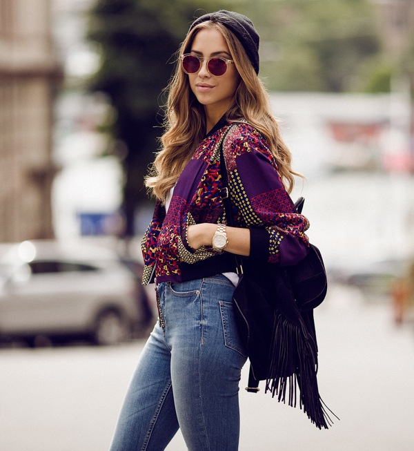 Kenza Zouiten is wearing jeans, tank top and bomber jacket from Monki, sunglasses from Le Specs and a bag from TopShop