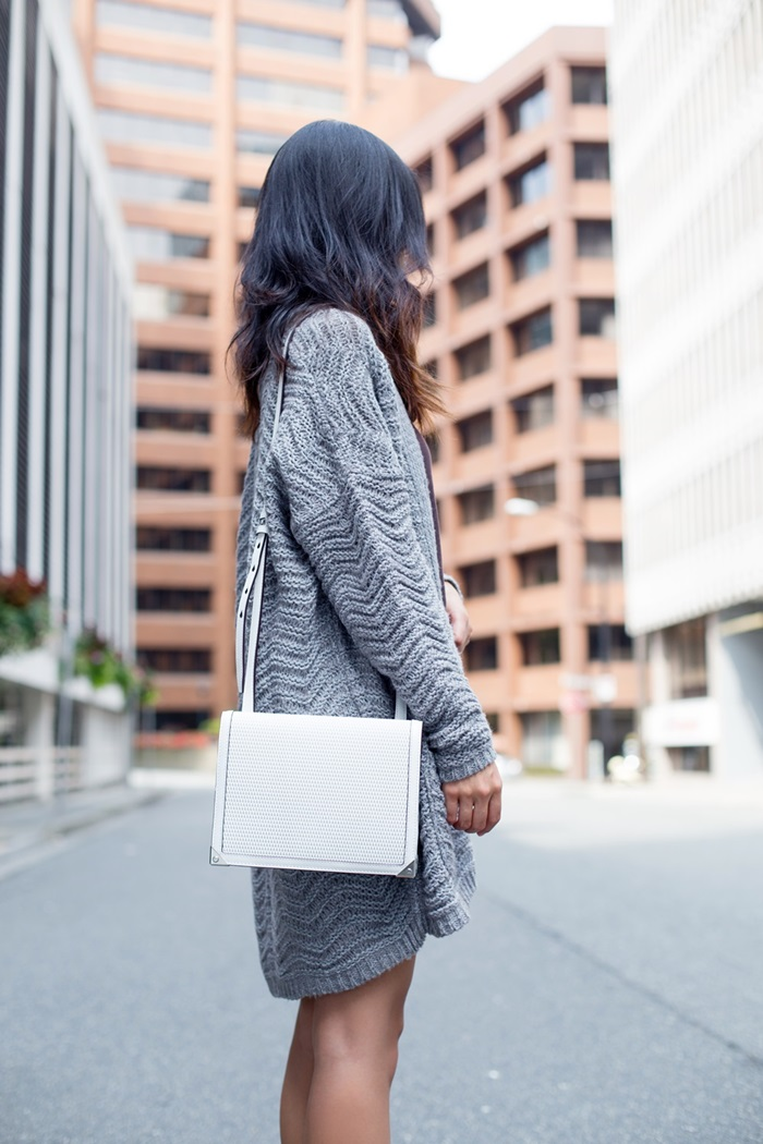 Claire Liu is wearing a pale blue Kimchi cardigan from Urban Outfitters and the bag is from Alexander Wang