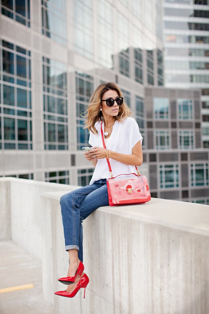 Christine Andrew is wearing a white silk blouse from Vince, boyfriend jeans, red shoes from Kurt Geiger, sunglasses from Karen Walker and the bag is from Marc Jacobs