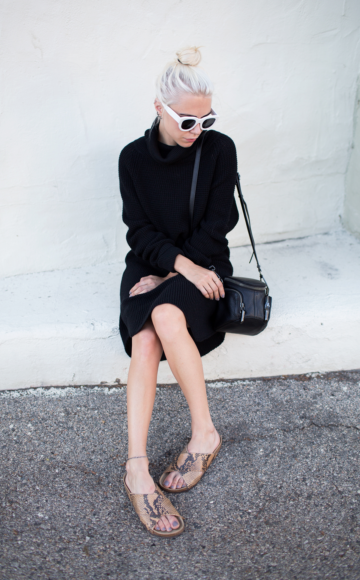 Courtney Trop is wearing a black oversized sweater dress and cross body bag from Aritzia Wilfred, sunglasses from Manifesto and snakeskin slides from Zara