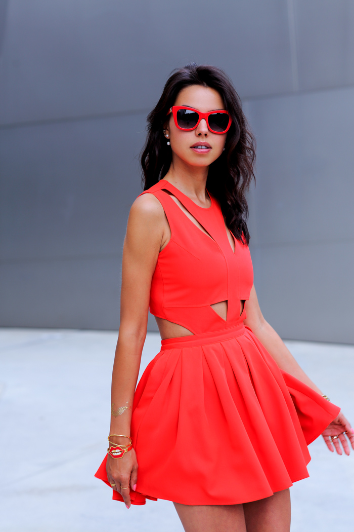 Annabelle Fleur is wearing a red dress from Lovers + Friends and matching sunglasses from Dolce & Gabbana