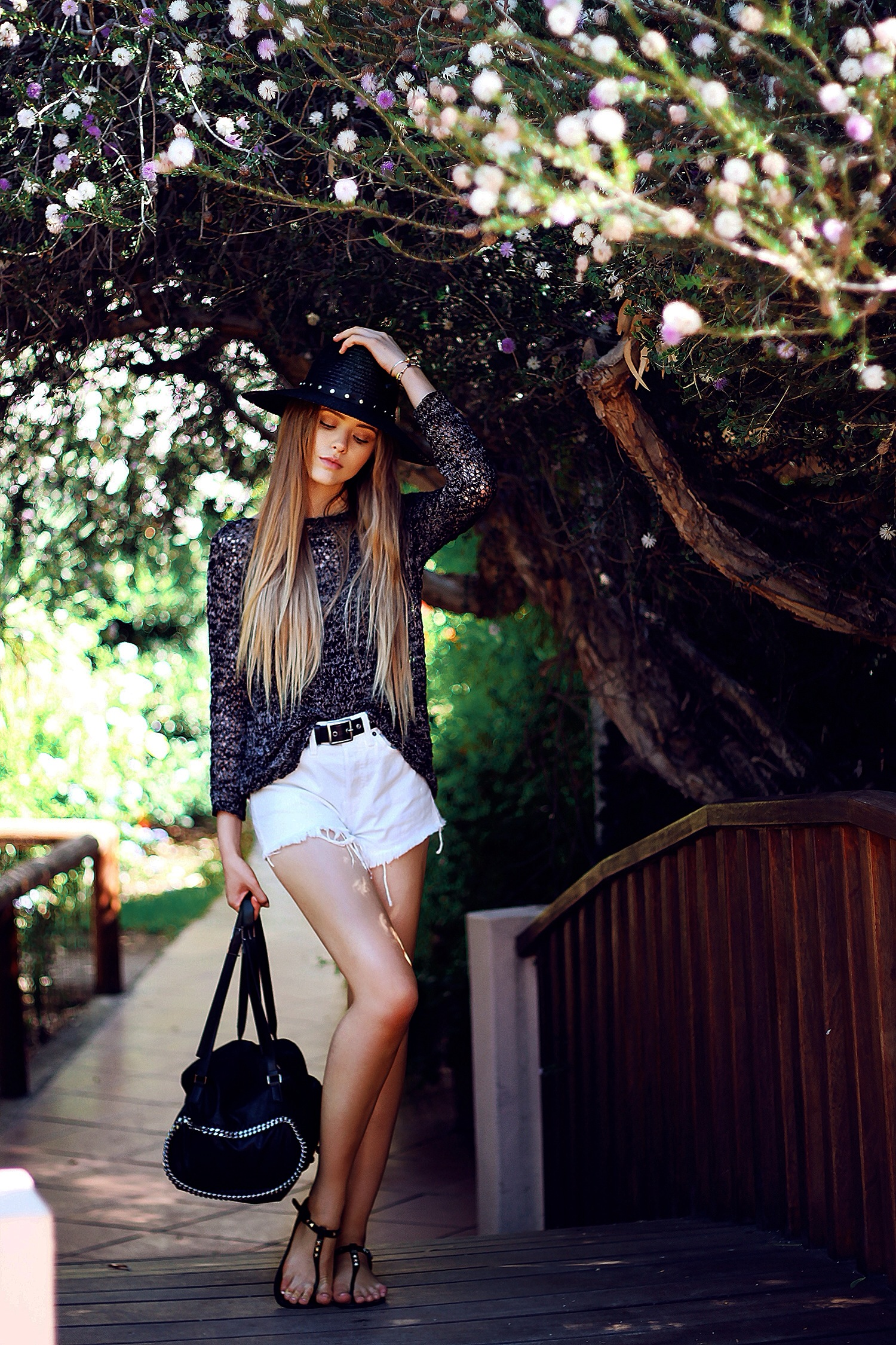 Kristina Bazan is wearing a sequin top, shorts from Guess, hat from The Kooples, shoes from Just Anna and a bag from Stella McCartney
