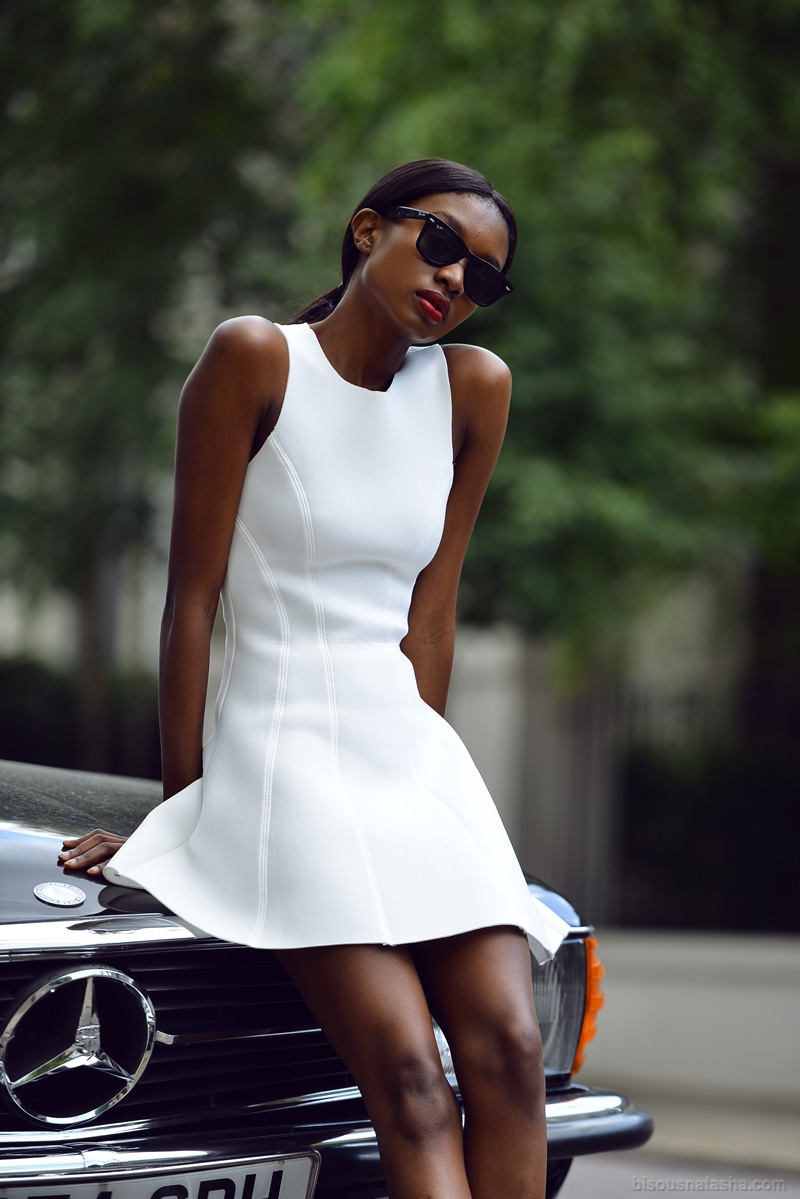 Natasha Ndlovu is wearing a white dress from TopShop and sunglasses from RayBan