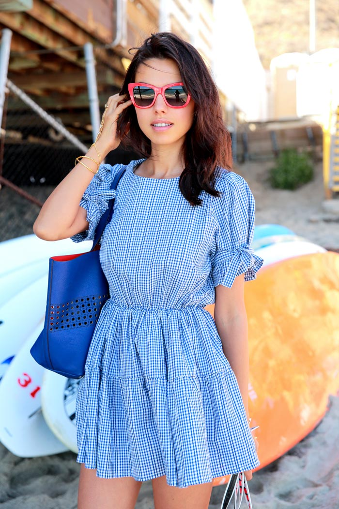Annabelle Fleur is wearing a blue and white check gingham dress from Pixie Market and red sunglasses from Dolce & Gabbana