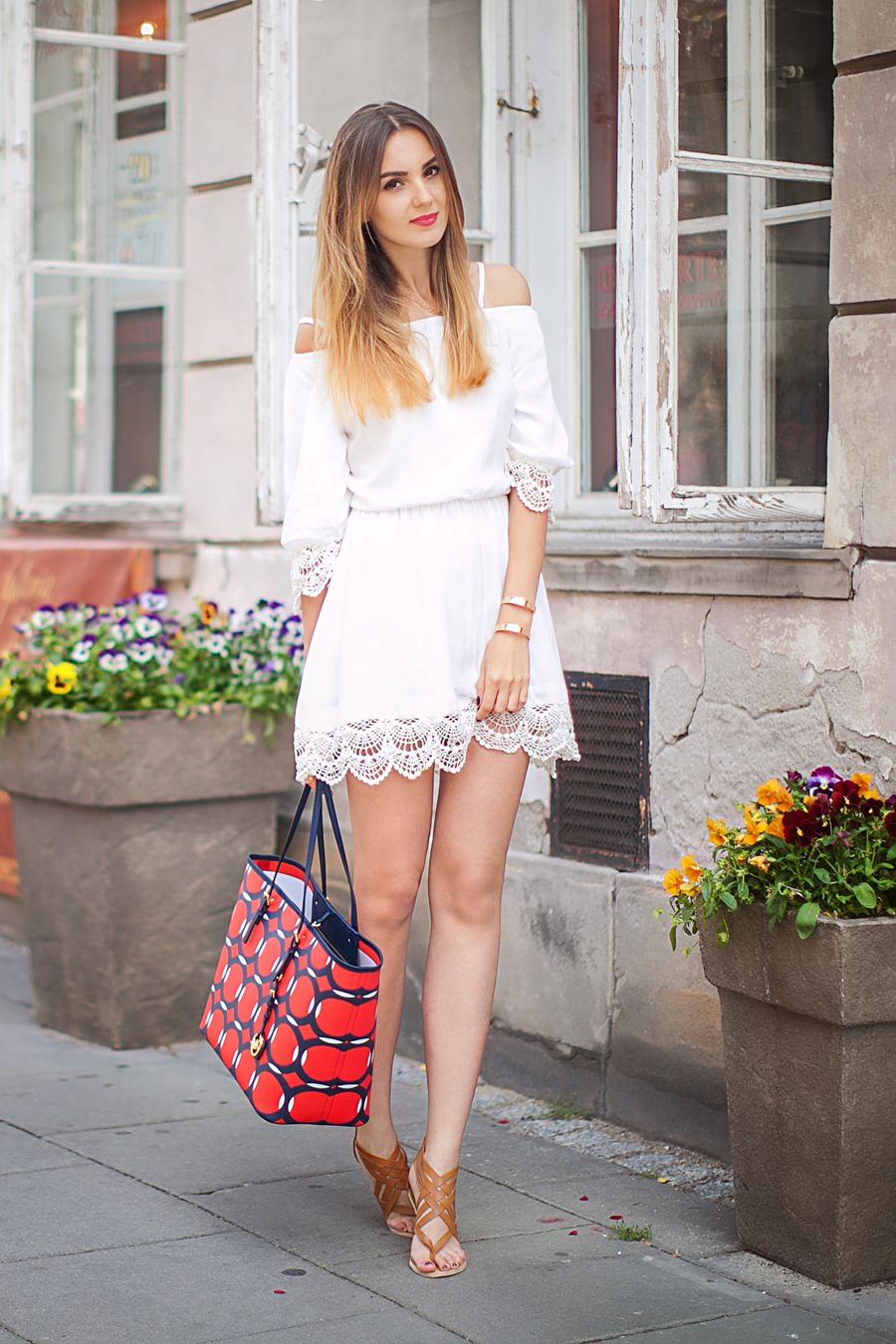 Nika Huk is wearing a white cotton dress with a crochet hem from Chicwish, sandals from Pull & Bear and a bag from Michael Kors
