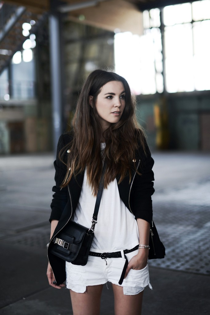 Cindy Van Der Heyden is wearing white ripped denim shorts from Zara, an oversized black jacket, T-shirt from H&M, and bag from Proenza Schouler
