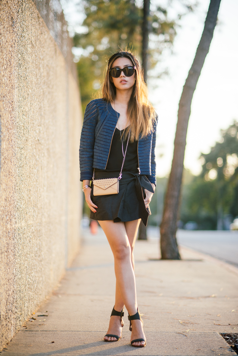 Jenny Ong is wearing a denim mesh jacket from Cynthia Rowley, black cami by J. Brand, black skirt by Isabel Marant, purse by Rebecca Minkoff, sandals from Jeffrey Campbell and sunglasses from Céline