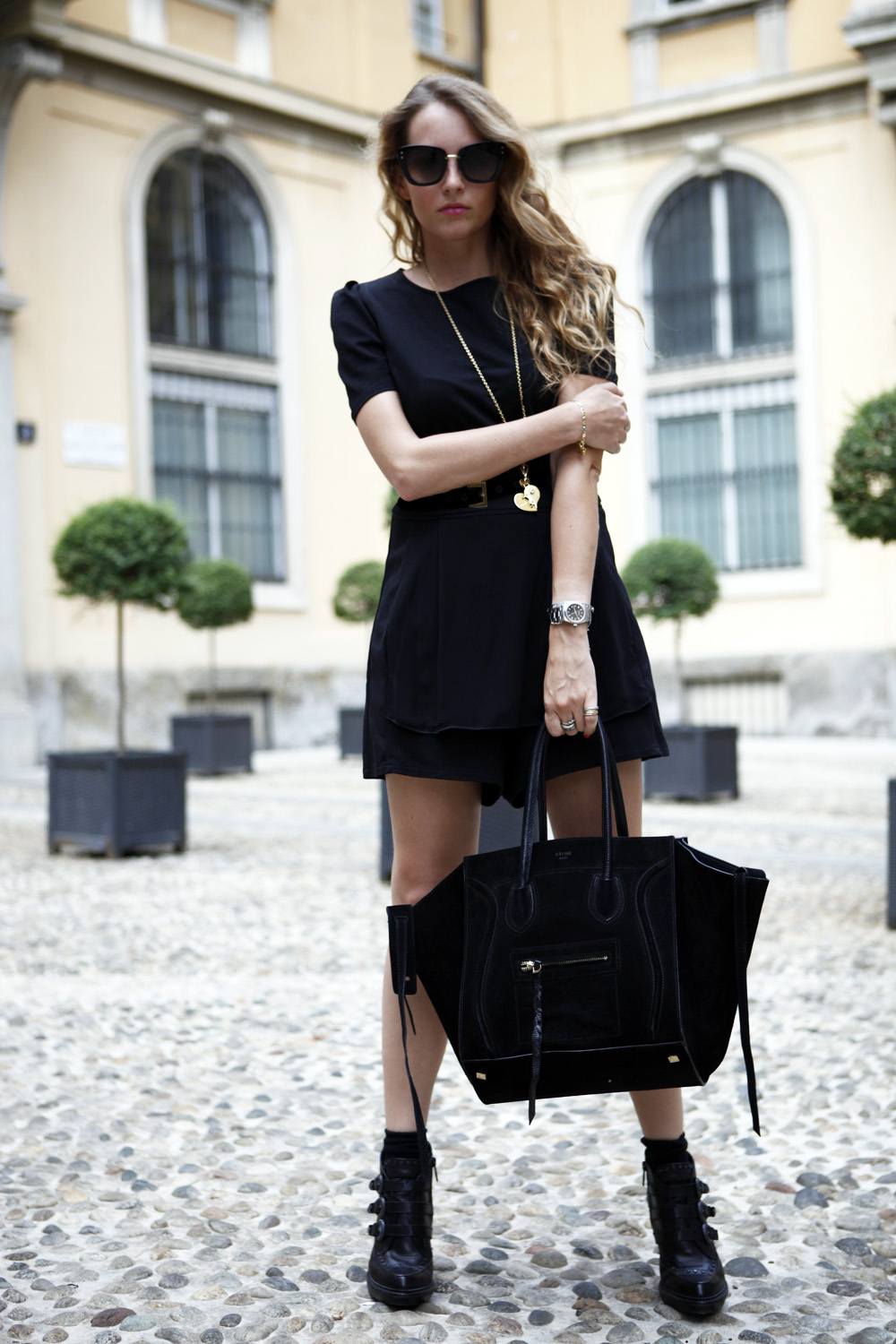 Virginia Varinelli is wearing all black shorts salopette from Stefanel, shoes from Ash, sunglasses from Marc Jacobs and bag from Celine