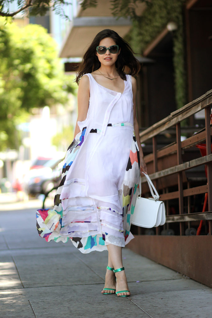 Adriana Gastelum is wearing a paint splash asymmetrical dress from Chloe, bag from Ferragamo and green sandals from Collage Boutique and matching sunglasses for Vogue Eyewear