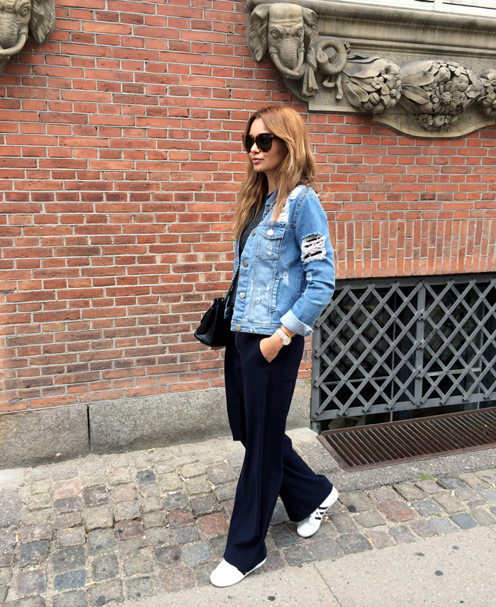 Funda Christophersen is wearing a ripped denim jacket from Gestuz, top from H&M, trousers from Zara, bag from Chanel, trainers by Adidas and sunglasses from Celine