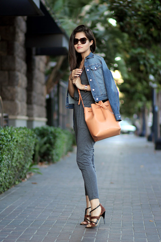 Adriana Gastelum is wearing a grey jumpsuit from Sheinside, denim jacket from Papaya, bag from Mansur Gavriel, shoes from Andrea and the sunglasses are from Karen Walker