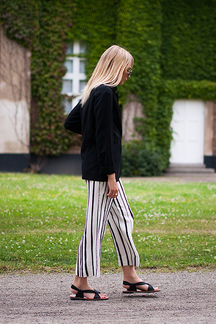 Charlotte Hellberg is wearing striped trousers from Zara, black jacket from COS, sandals and sunglasses from & Other Stories