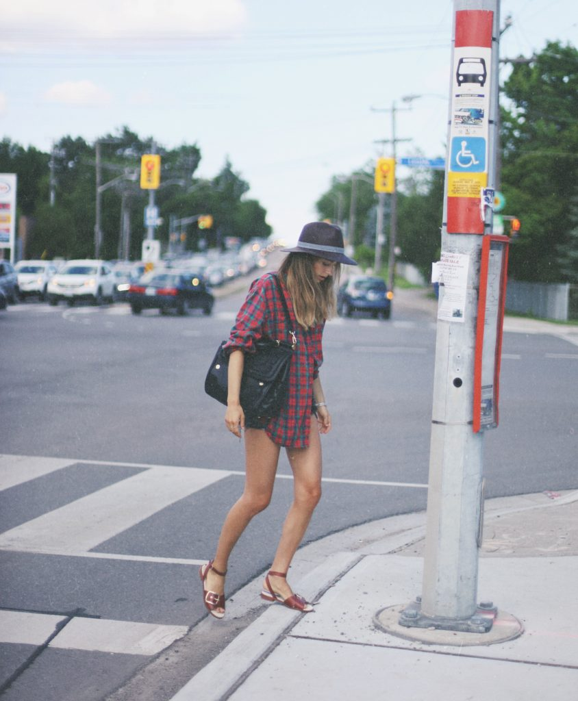 Sonya Esman is wearing a vintage plaid shirt, denim shorts from Levi's, sandals from Zara, hat from Worth & Worth and bag from Dolce Gabbana