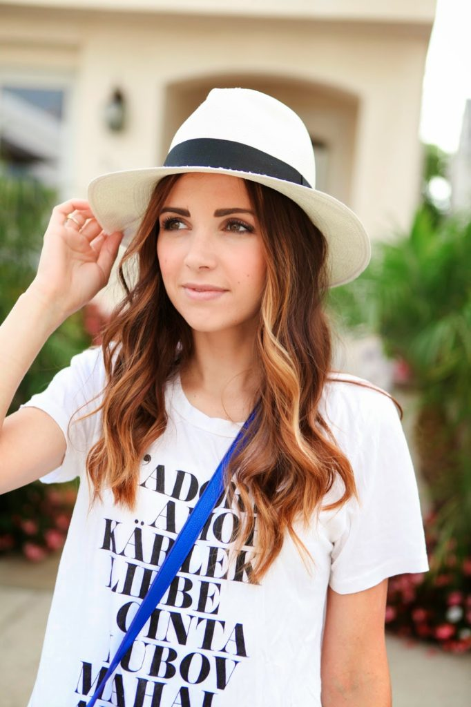 Merrick White is wearing a graphic statement T-shirt and panama hat from J. Crew