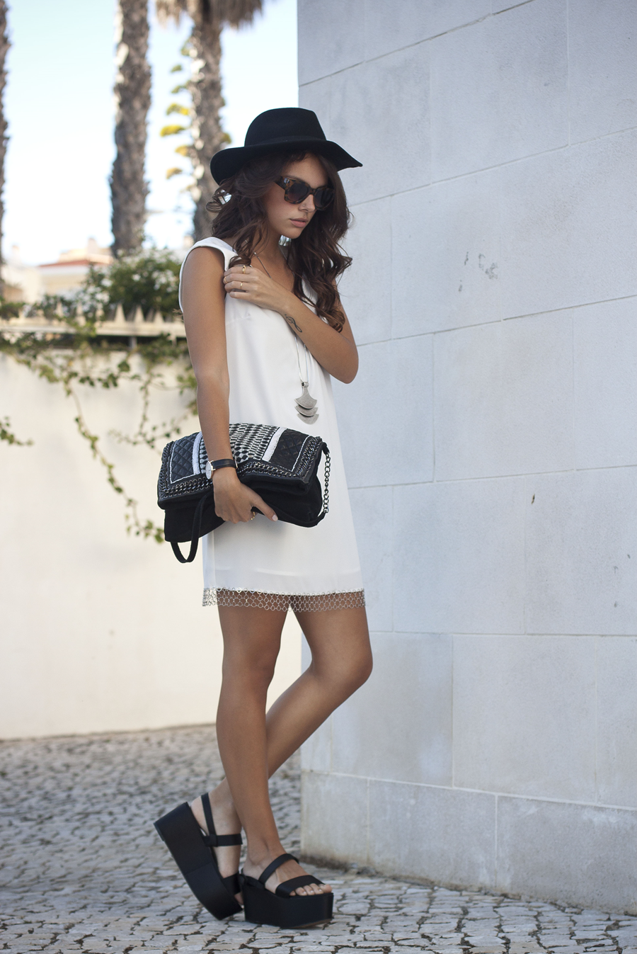 Mafalda Castro is wearing a white dress from ÂMÈ Concept and bag and shoes from Zara, sunglasses from Zero UV