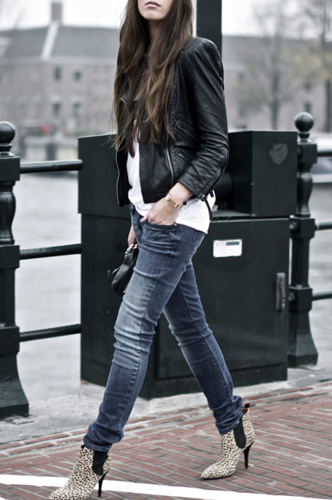 Cindy Van Der Heyden is wearing jeans from Levi's, leather jacket and clutch from Zara, T-shirt from TopShop, and leopard ankle boots from Isabel Marant