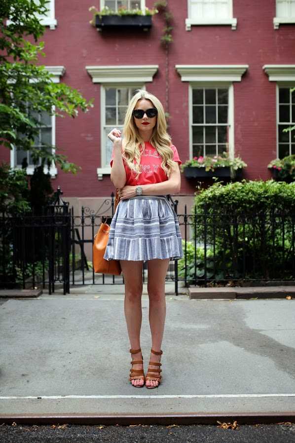 Blair Eadie is wearing a red top from Sincerely Jules, grey and white pattern skirt from Joa, shoes from French `Connection and the orange bag is from Mansur Gavri