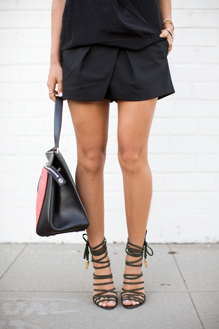 Aimee Song is wearing black sleeveless blouse from Helena Quinn, matching pleated shorts from Tibi, sshoes from Giuseppe Zanotti and the bag is from Celine