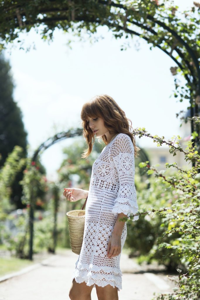 Louise Ebel is wearing a white crochet dress from  Chicwish and the bag is from L'Occitane
