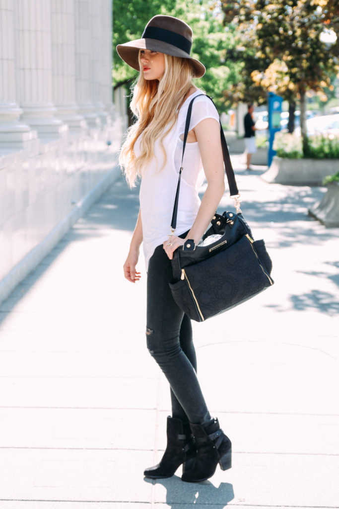 Amber Fillerup Clark is wearing a white top from Helmut Lang, black distressed jeans and boots from Rag & Bone and a floppy fedora from Nordstrom