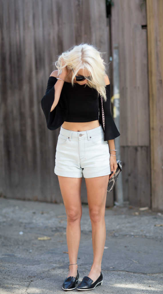 Courtney Trop is wearing a black top from Reformation, shorts from Objects Without Meaning and shoes from Acne
