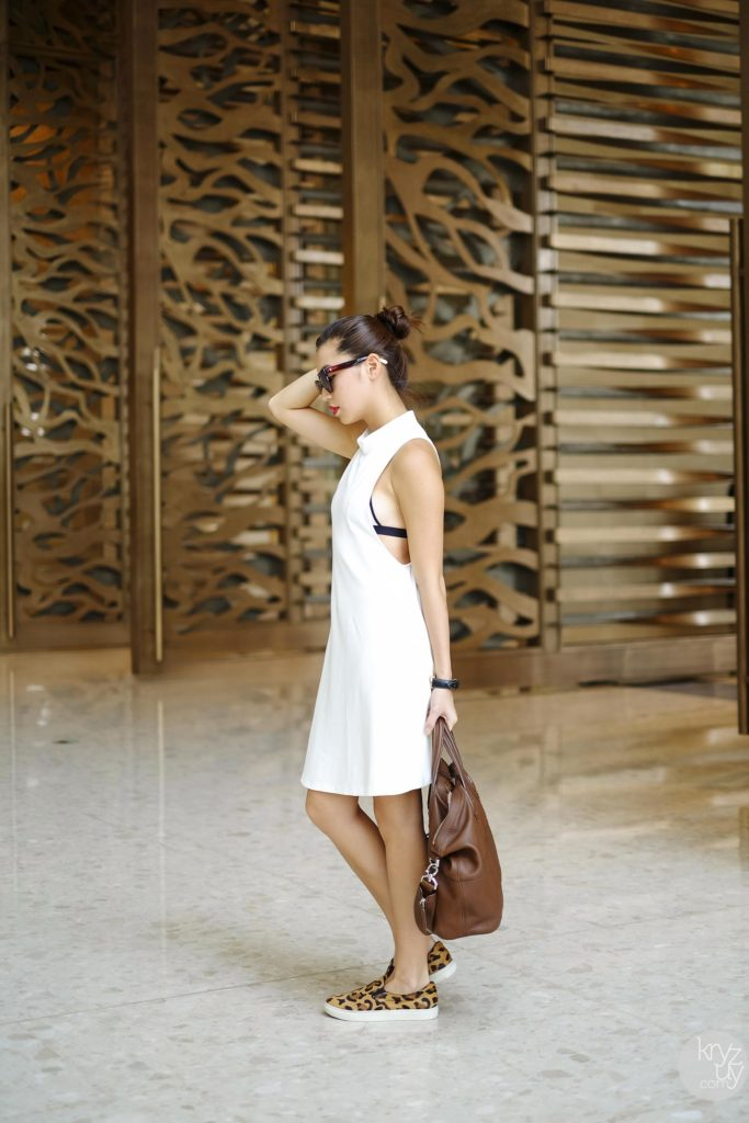 Kryz Uy is wearing a a white dress from Sheinside, bra from Triangl, sunglasses from Triwa and leopard print slip-ons from Steve Madden
