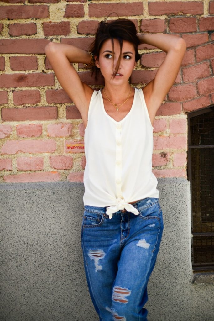 Alexandra Pereira is wearing a knot tied top from Strena Moda and ripped jeans from SuiteBlanco