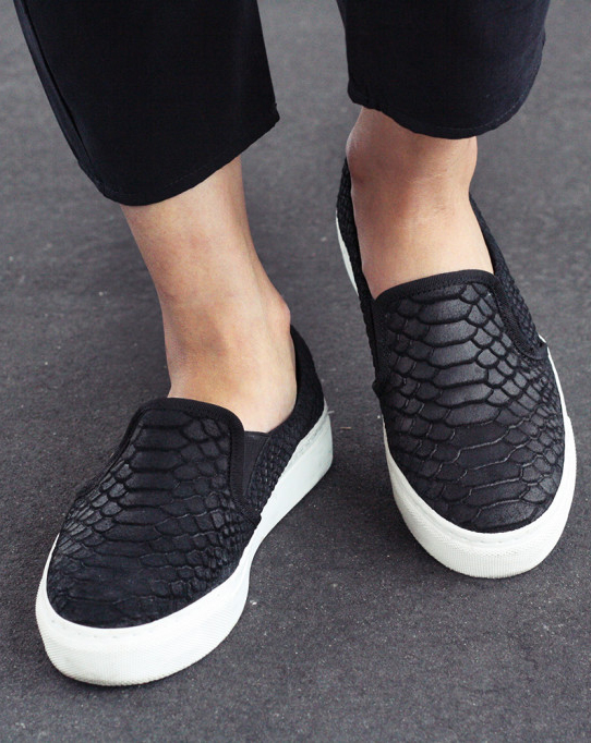 Thao Nhi Le is wearing black slip-ons from Oxmox