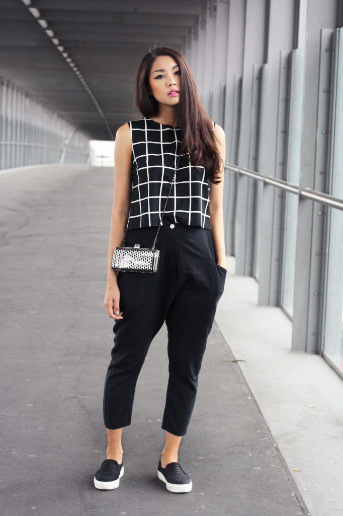 Thao Nhi Le is wearing black baggy trousers and grid top from Mango and slip-ons from Oxmox