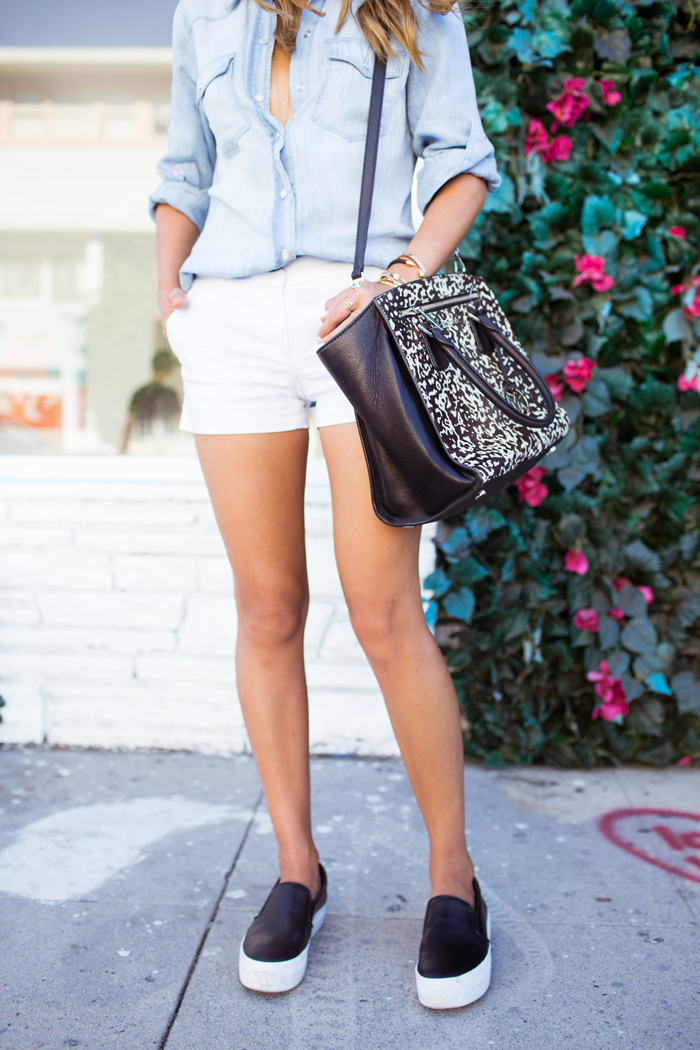 Aimee Song is wearing a casual denim shirt, white shorts, slip-ons and bag all from Michael Kors
