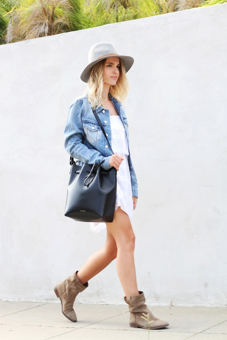 Mija is wearing a denim jacket from Acne Studios, white summer dress from Mango, felt hat from Janessa Leone, bucket bag from Mansur Gavriel and boots from Isabel Marant