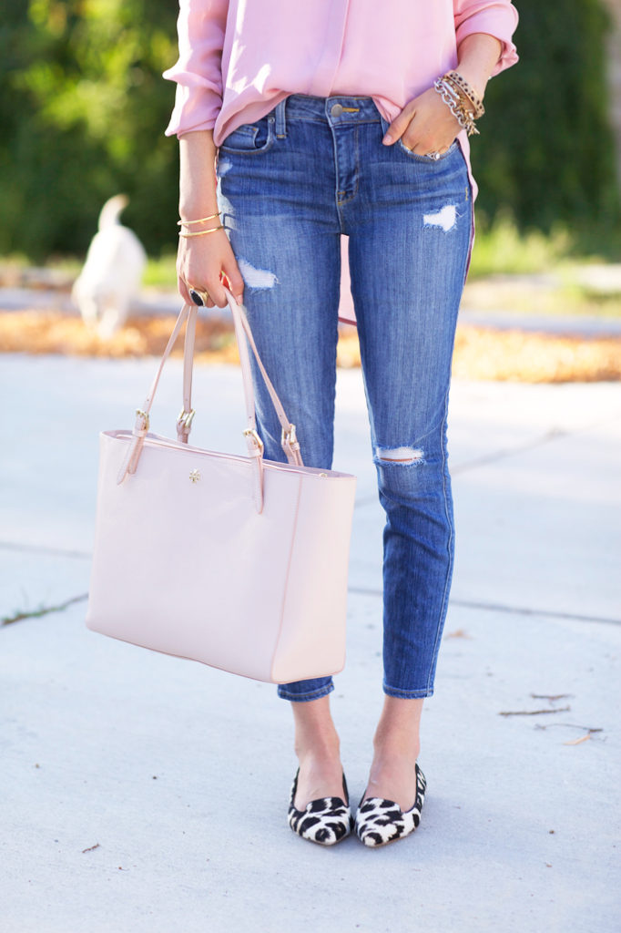 Rachel Parcell is wearing a pink top and shoes from J. Crew, distressed jeans from Current/Elliott, pink bag from Tory Burch and sunglasses from Karen Walker